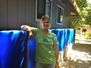 Jesse Froehlich '08 with one of the rainwater collection systems she designed and installed.